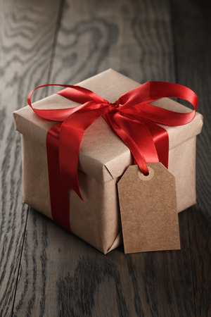 31539032 - rustic gift box with red ribbon bow and empty tag, on old wood table